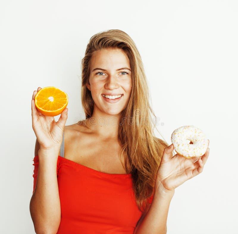 Jonge blondevrouw die tussen doughnut en oranje fruitisola kiezen royalty-vrije stock afbeelding