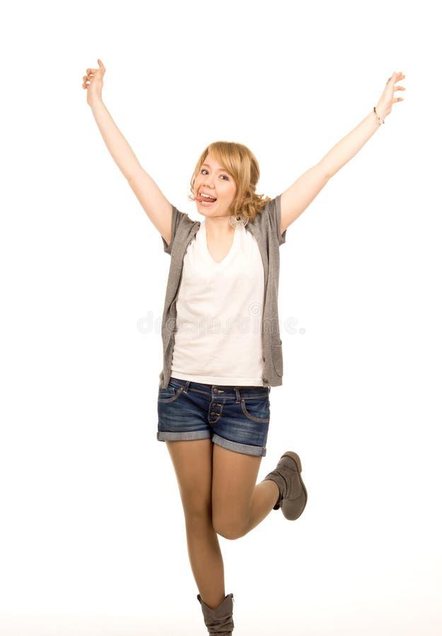Jonge blondevrouw die voor vreugde springen stock afbeelding