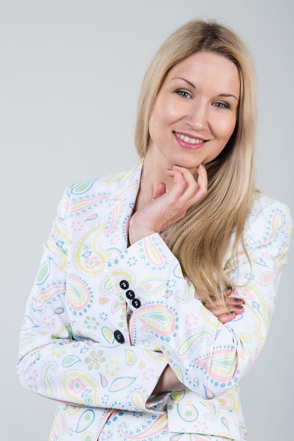 jonge blondevrouw in een wit jasje stock foto's