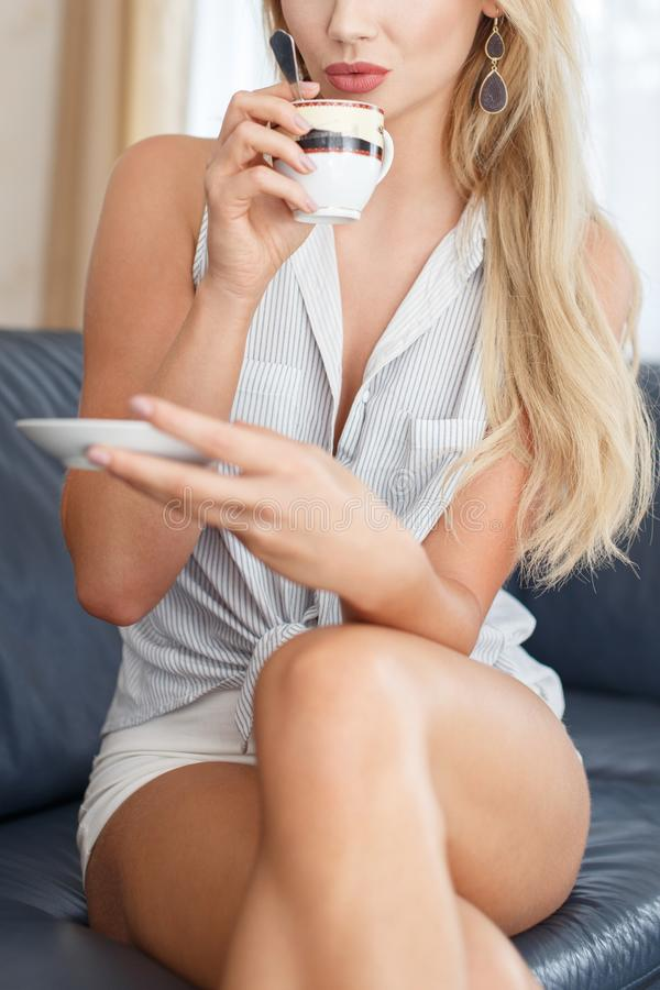 Jonge blondevrouw het drinken koffie op bank stock foto