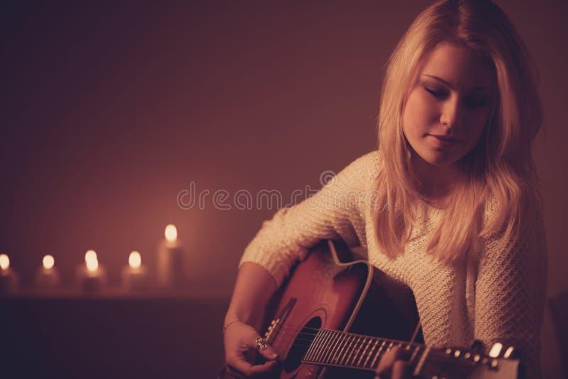 Jonge blondevrouw het spelen gitaar in kaarslicht stock fotografie