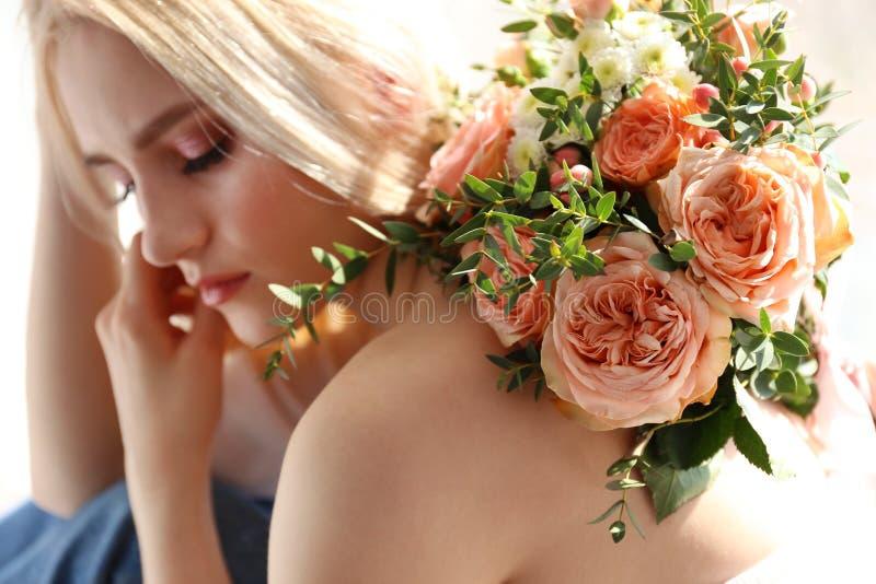 Jonge blondevrouw in mammajeans en de holdingsboeket van het gewassen hoogste overhemd van tulpen royalty-vrije stock afbeeldingen