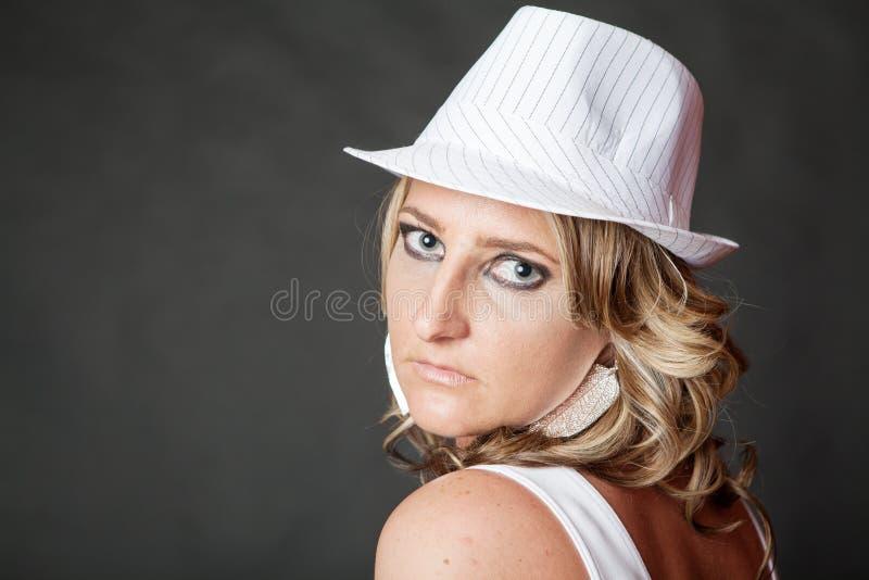 Jonge blondevrouw met ernstig gezicht die witte hoed dragen royalty-vrije stock afbeelding
