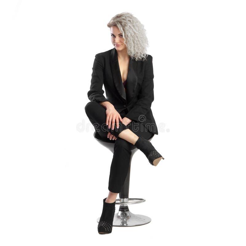 Jonge blondevrouw met krullend haar in zwart pak royalty-vrije stock fotografie