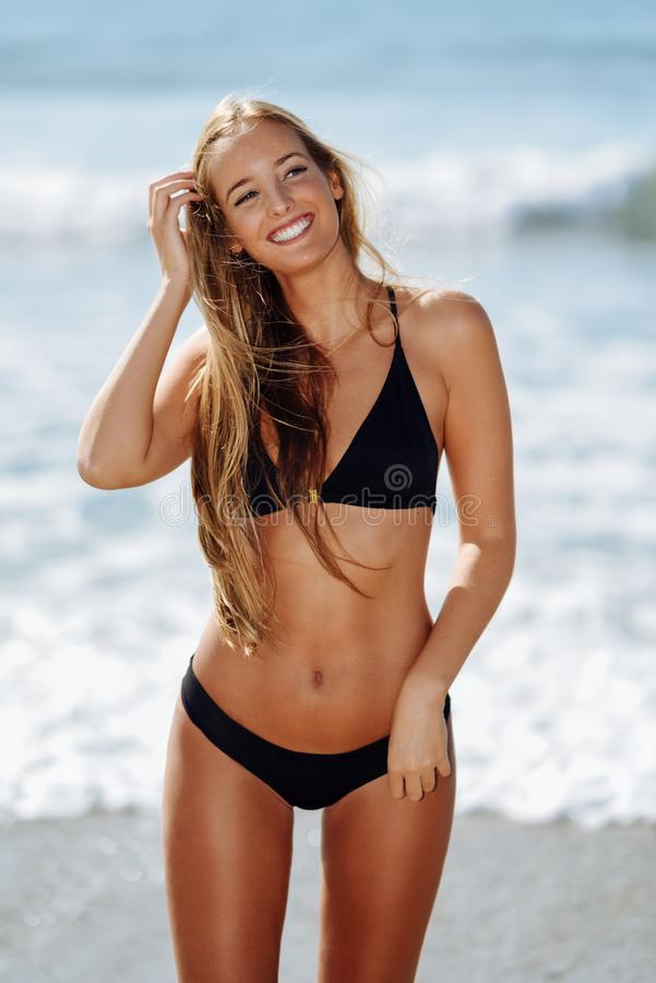 Jonge blondevrouw met mooi lichaam in het swimwear glimlachen op a royalty-vrije stock foto's