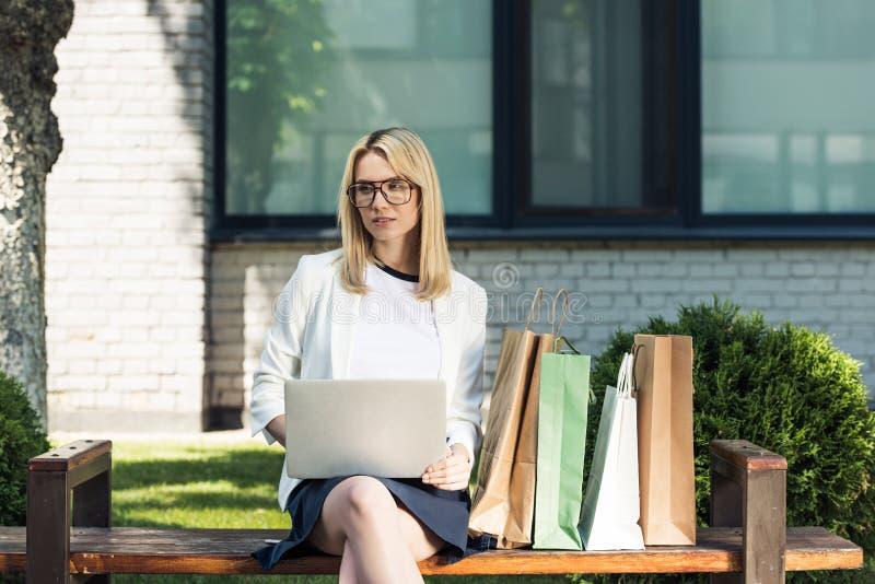 jonge blondevrouw in oogglazen die laptop met behulp van terwijl het zitten op bank stock foto