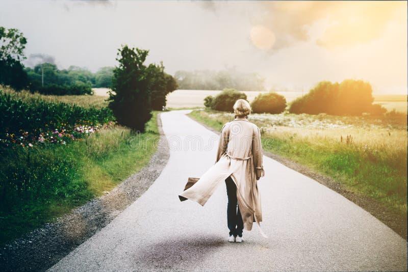 Jonge blondevrouw in stromende lange overjas die zich in midden van het winden van weg bevinden royalty-vrije stock afbeeldingen