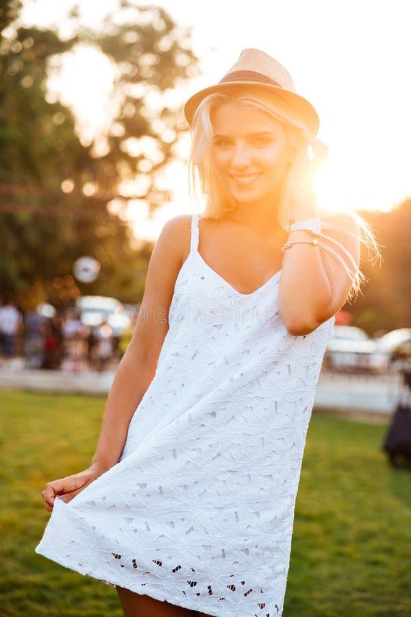 Jonge blondevrouw witte kleding dragen en hoed die in openlucht stellen royalty-vrije stock afbeeldingen