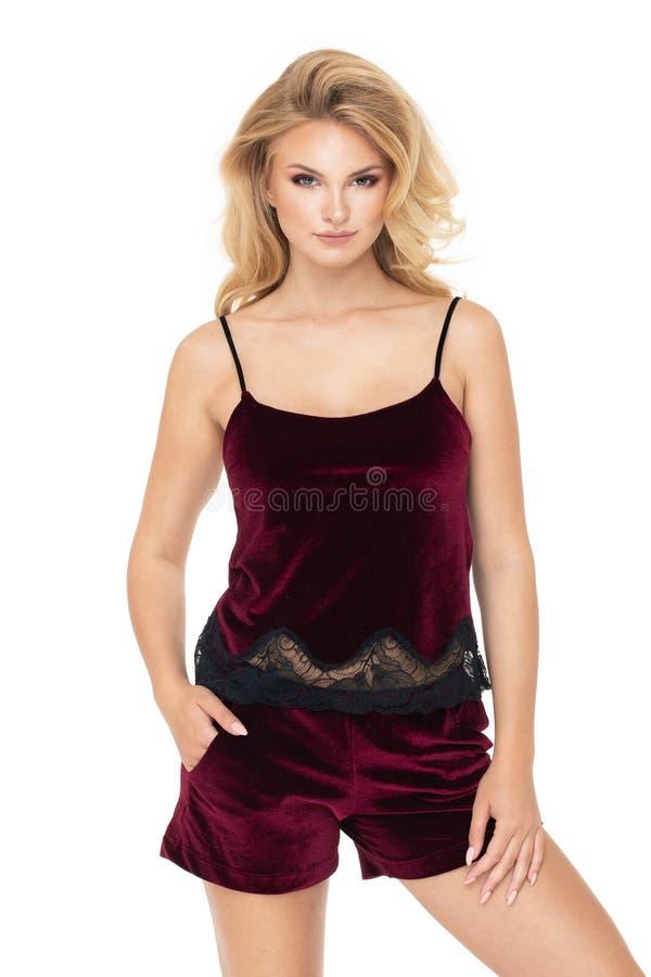 Jonge blondevrouw in zwart die ondergoed, op witte achtergrond wordt geïsoleerd stock foto