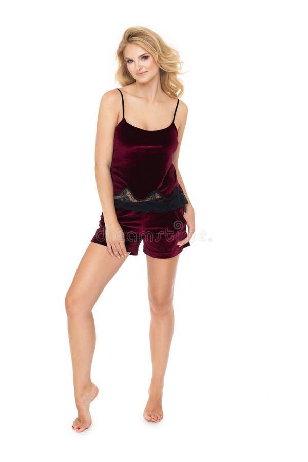 Jonge blondevrouw in zwart die ondergoed, op witte achtergrond wordt geïsoleerd stock fotografie
