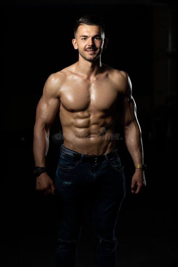 Jonge Bodybuilder die in Jeans Spieren buigen stock afbeeldingen