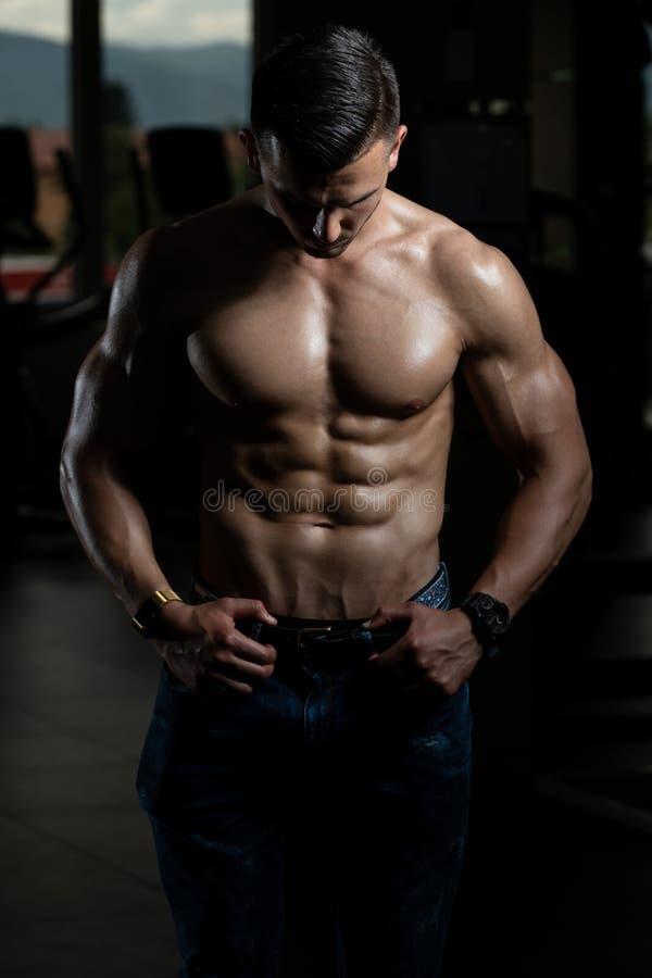 Jonge Bodybuilder die in Jeans Spieren buigen royalty-vrije stock foto's