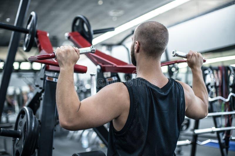 Jonge Bodybuilder die Zwaargewicht Oefening voor terug op Machine doen stock afbeelding
