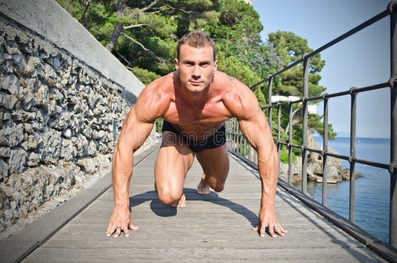 Jonge bodybuilder klaar aan sprint en looppas stock afbeelding
