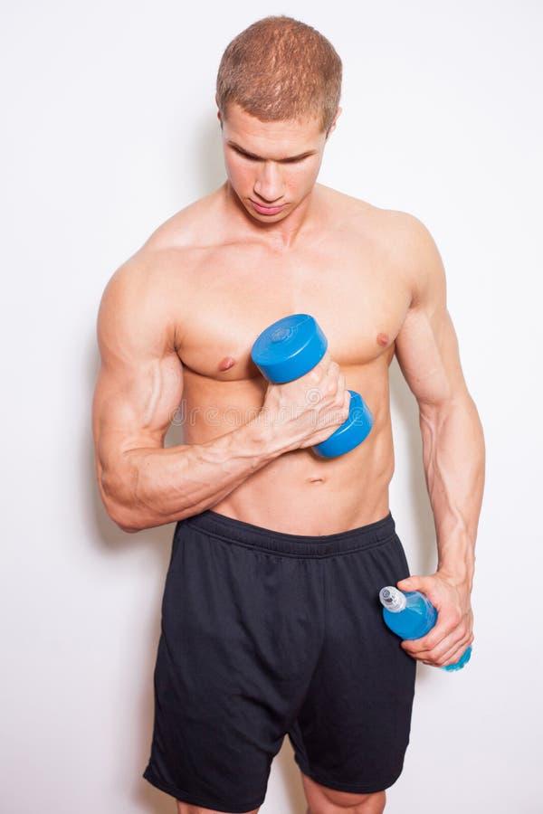 Jonge bodybuilder zonder overhemd die een blauwe domoor opheffen. In oth royalty-vrije stock foto's