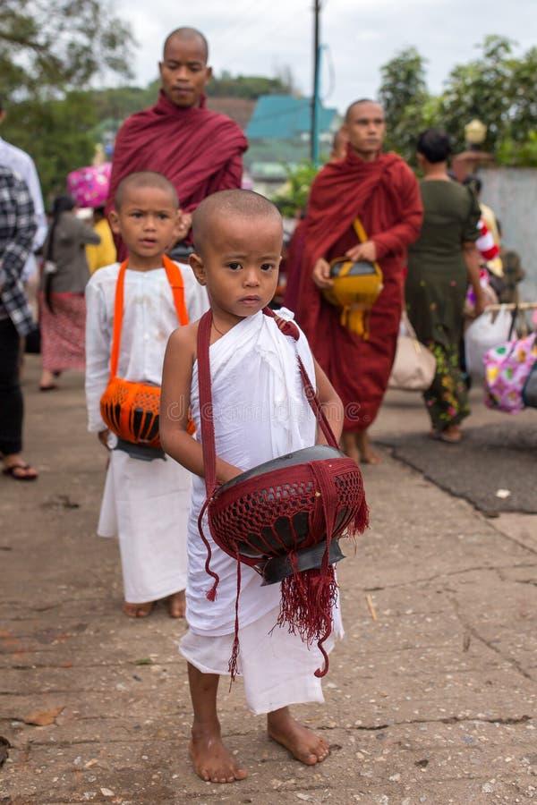 Jonge boeddhistische beginners en monniken die dagelijkse aalmoes verzamelen dichtbij de Kyaiktiyo-pagode of de Gouden rots, Myan royalty-vrije stock afbeeldingen