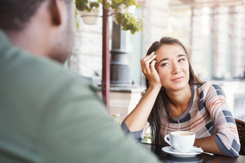 Jonge bored meisje het drinken koffie op datum bij een koffie stock afbeeldingen