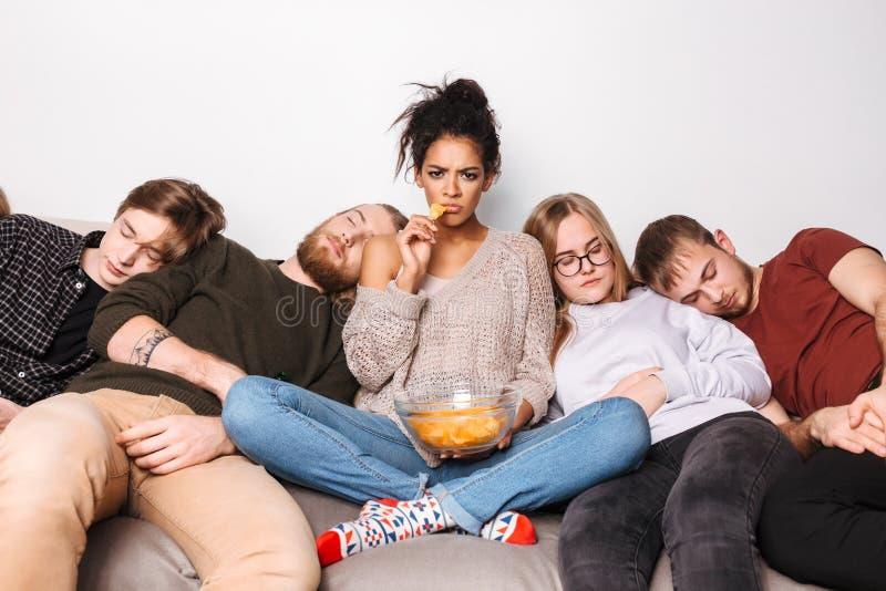Jonge boze dame die droevig in camera en chips eten terwijl haar vrienden die thuis slapen dichtbij kijken royalty-vrije stock fotografie