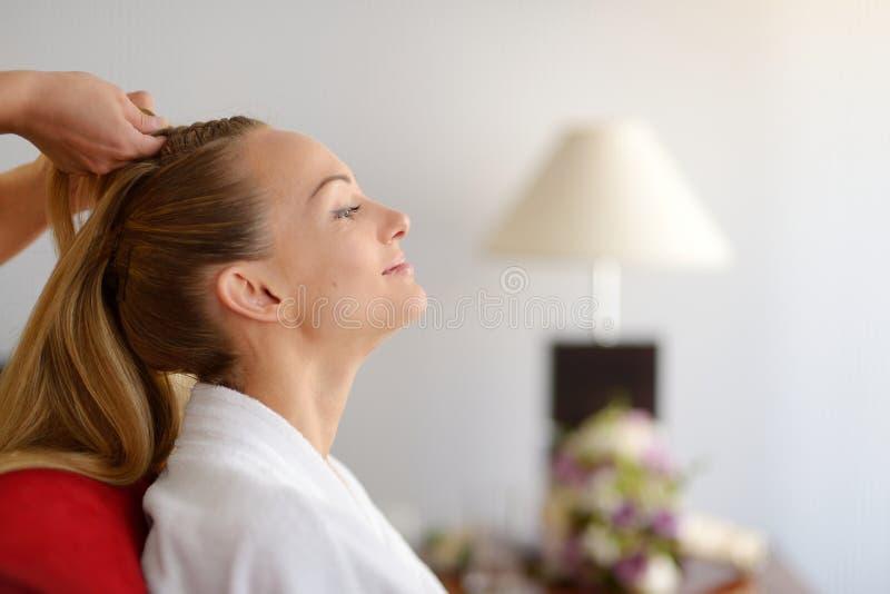 Jonge bruid die haar haar gedaan krijgen stock afbeeldingen