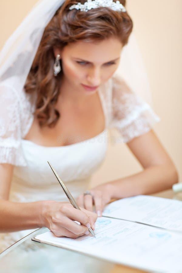 Jonge bruid die huwelijksdocumenten ondertekent royalty-vrije stock fotografie
