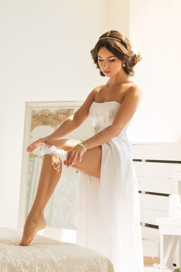 Jonge bruid die kouseband op haar been zetten stock foto
