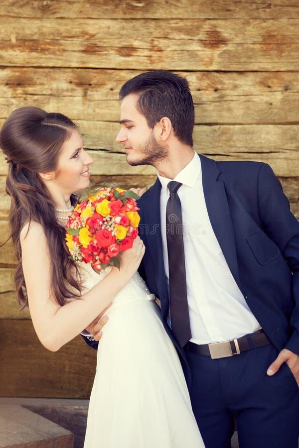 Jonge bruid en bruidegom die elkaar met liefde bekijken stock afbeeldingen