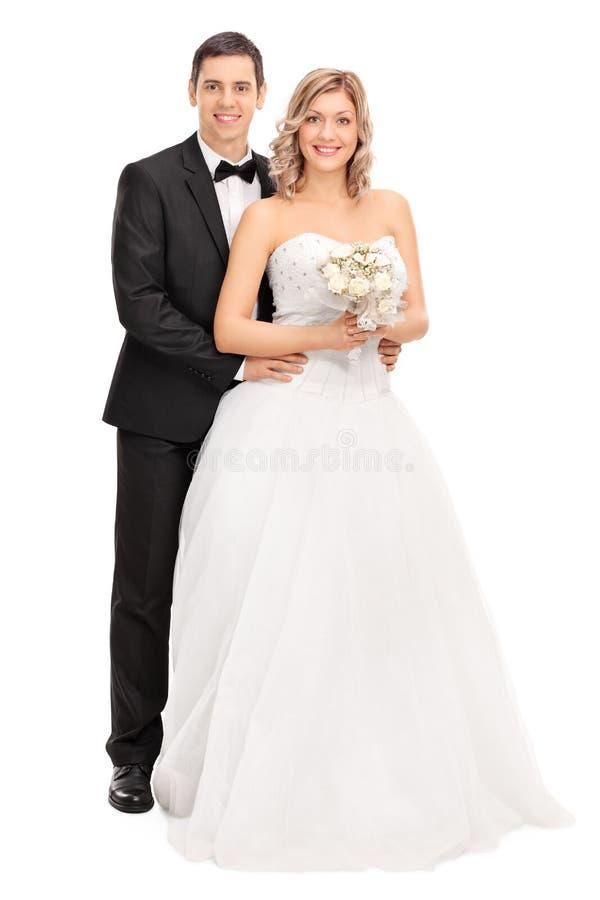 Jonge Bruid en Bruidegom die samen stellen stock fotografie