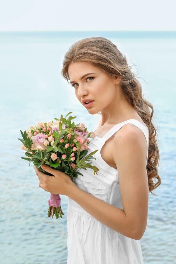 Download Jonge Bruid In Het Witte Boeket Van De Togaholding Stock Afbeelding - Afbeelding bestaande uit holding, seashore: 107702637