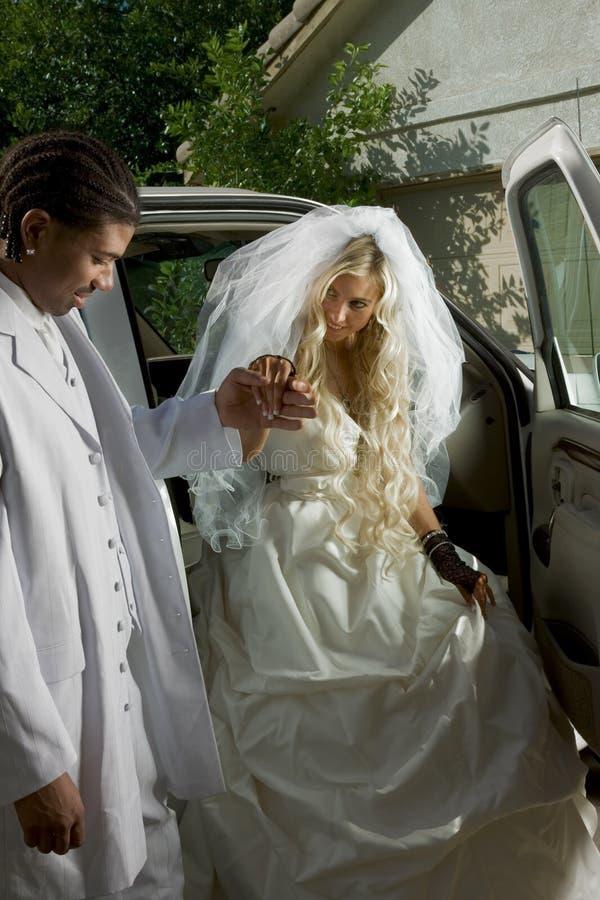 Jonge bruid in huwelijkskleding die van auto krijgt royalty-vrije stock afbeelding