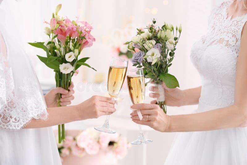 Jonge bruiden die boeketten van mooie bloemen en glazen met champagne houden royalty-vrije stock fotografie