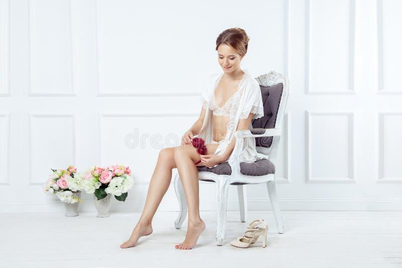 Jonge bruidzitting op uitstekende stoel en het zetten op bloemengarte royalty-vrije stock afbeelding
