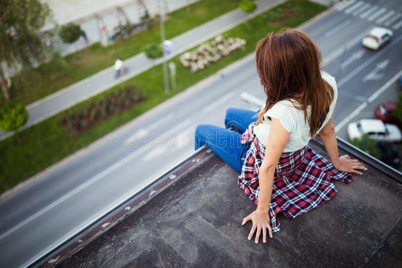 Jonge bruine haired meisjeszitting op dak stock afbeelding