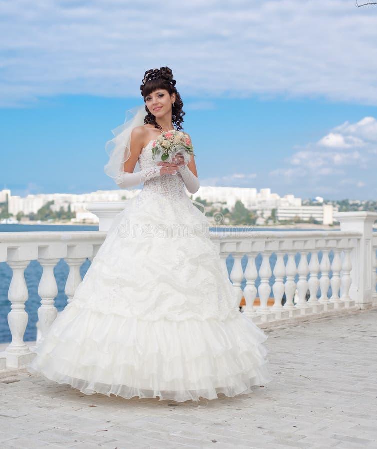 Jonge brunette in huwelijkskleding die in openlucht stelt stock foto's