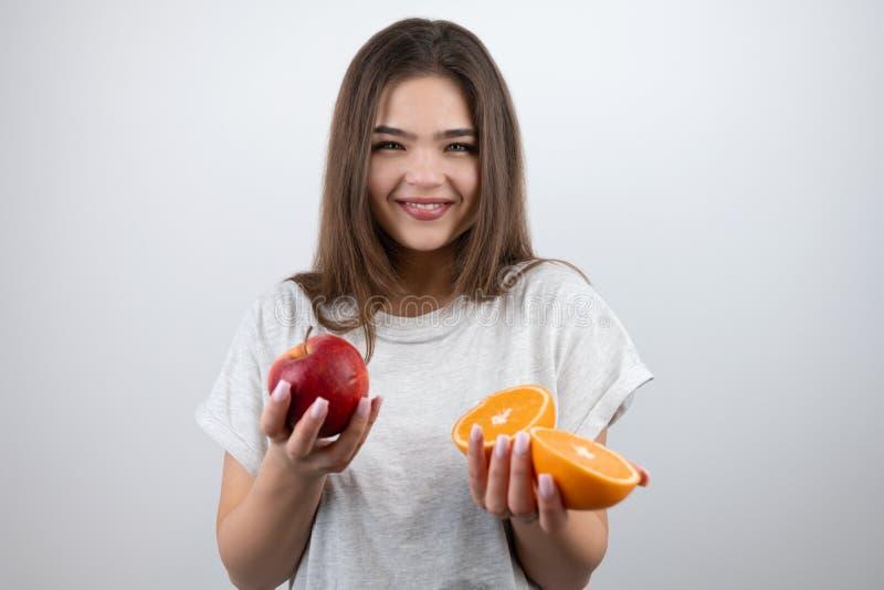 Jonge brunette vrouw met twee helften sinaasappelen in één hand en rode appel in een andere glimlach, die op geïsoleerd wit staat stock afbeeldingen
