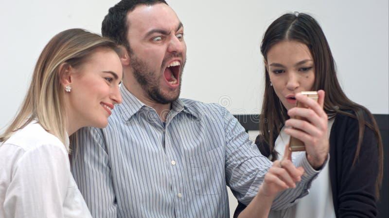 Jonge bureaumedewerkers die pret hebben die selfies op de telefoon nemen stock foto's