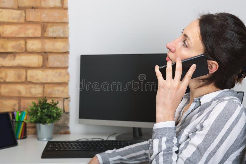 Jonge bureauvrouw die aan iemand op haar mobiele telefoon spreken stock afbeelding