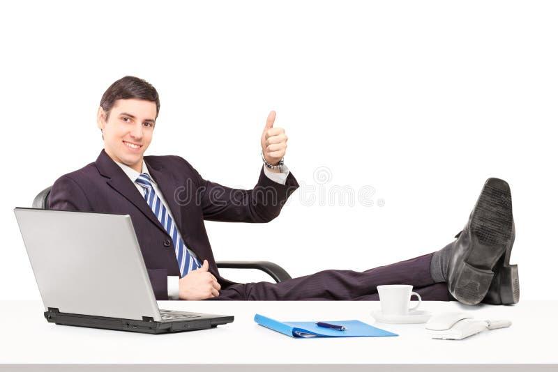 Jonge businesspersonzitting op een stoel met zijn benen omhoog en giv royalty-vrije stock fotografie