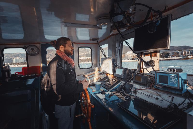 Jonge Capitan met Baard bevindt zich bij het Roer en controleert het Schip, Mening van binnenuit Kapiteins` s Cabine stock afbeeldingen