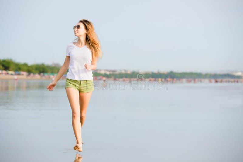 Jonge caucasionvrouw die op het strand lopen bij royalty-vrije stock fotografie