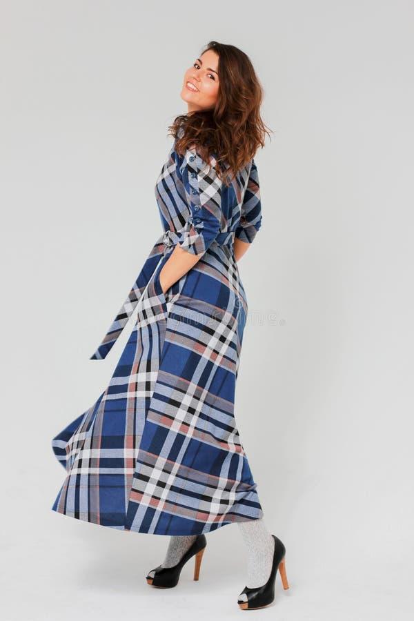 Jonge charmante donkerbruine vrouw met krullend haar in lange plaid blauwe kleding stock afbeeldingen