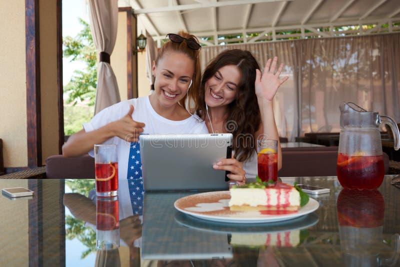 Jonge charmante vrouwen met mooie glimlachen die videoconferentie op aanrakingsstootkussen hebben terwijl het zitten in koffiewin stock fotografie
