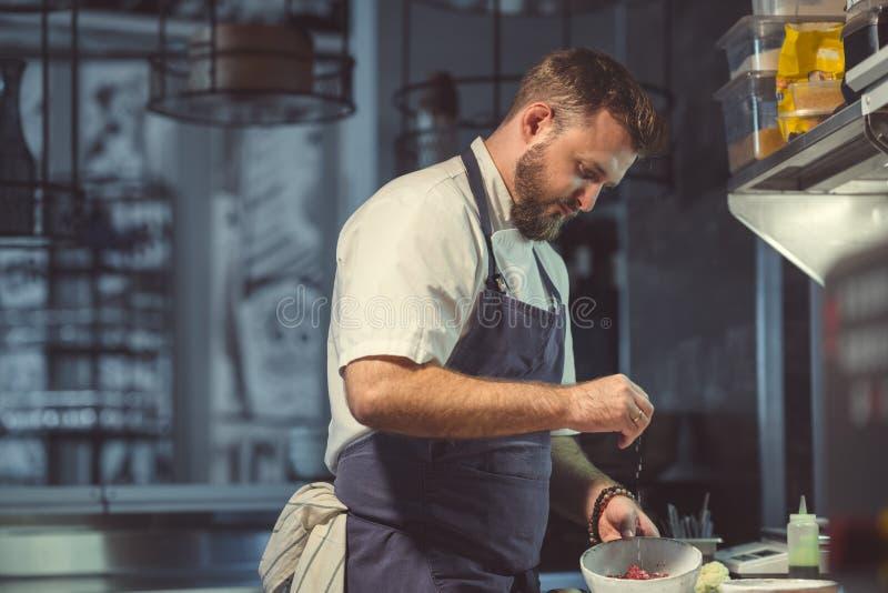 Jonge chef-kok die binnen koken stock afbeeldingen