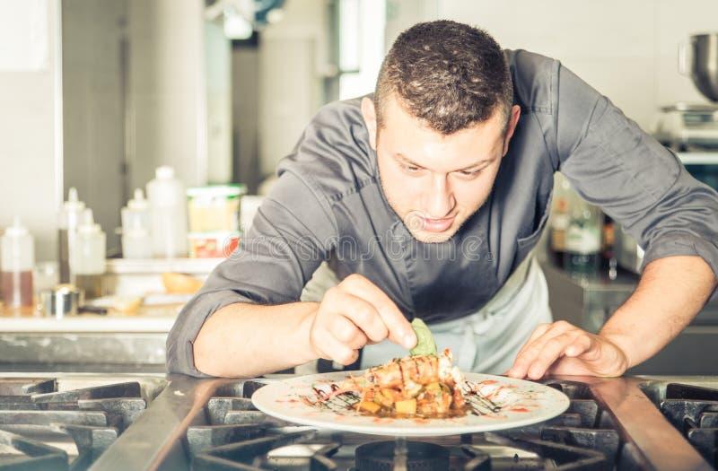 Jonge chef-kok die een smakelijke maaltijd voorbereiden royalty-vrije stock fotografie