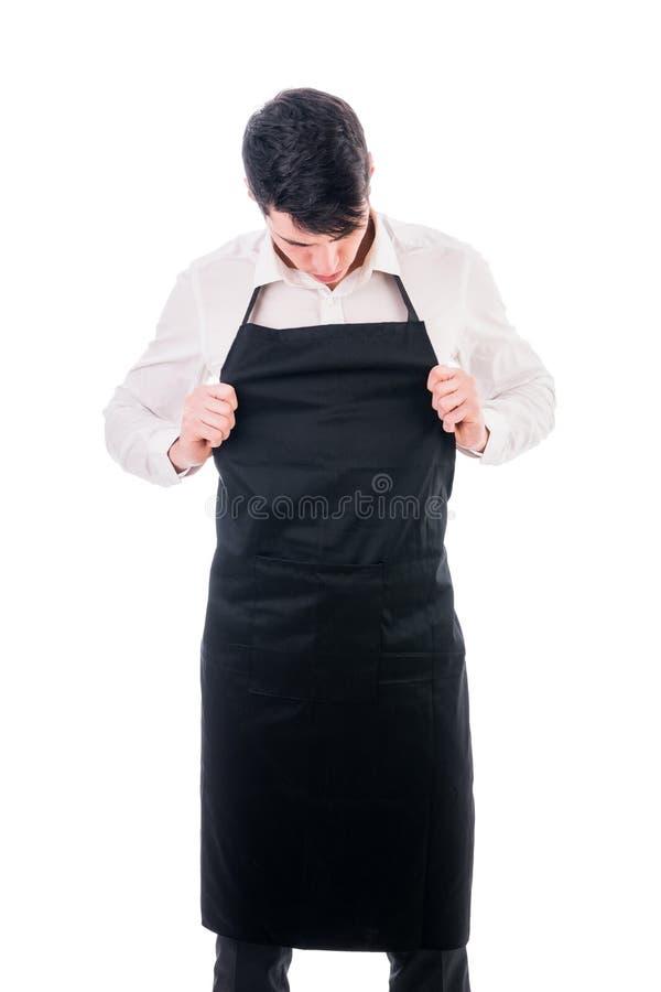 Jonge chef-kok of kelner die zwarte geïsoleerde schort dragen royalty-vrije stock afbeeldingen