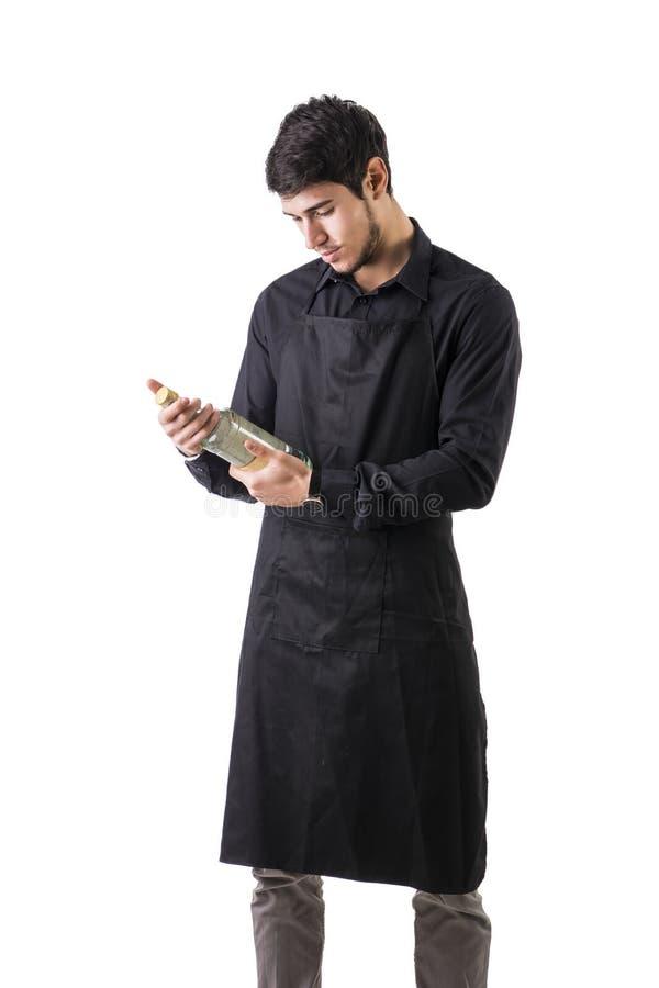 Jonge chef-kok of kelner die zwarte geïsoleerde schort dragen royalty-vrije stock foto's