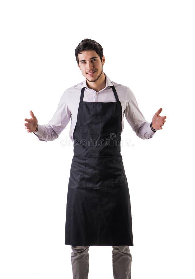 Jonge chef-kok of kelner die zwarte geïsoleerde schort dragen royalty-vrije stock fotografie