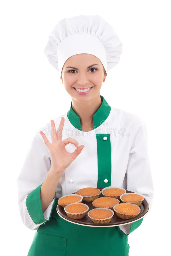 Jonge chef-kokvrouw in eenvormig holdingsdienblad met muffins en showin stock afbeeldingen