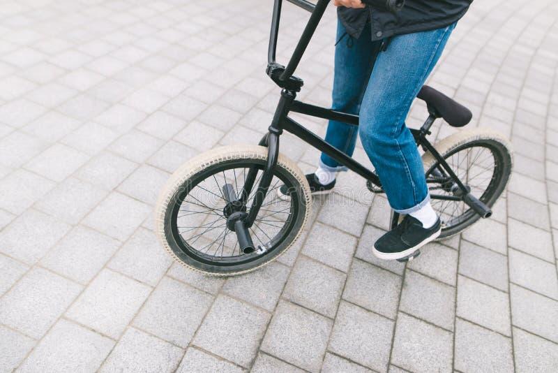 Jonge chelovek zit op een BMX-fiets BMX met benenclose-up BMX-concept Straatcultuur royalty-vrije stock foto's