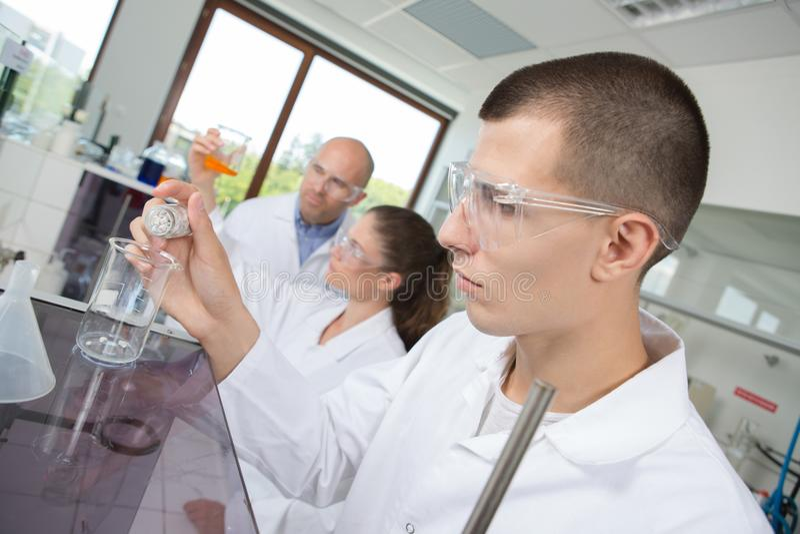 Jonge chemicus die chemische vloeistof in laboratorium combineren royalty-vrije stock foto's