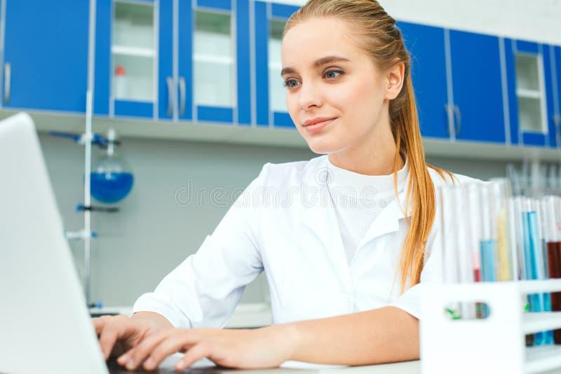Jonge chemieleraar in de werkplaats die van het schoollaboratorium laptop close-up gebruiken royalty-vrije stock afbeelding
